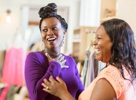 Two African American women laughing in clothing store