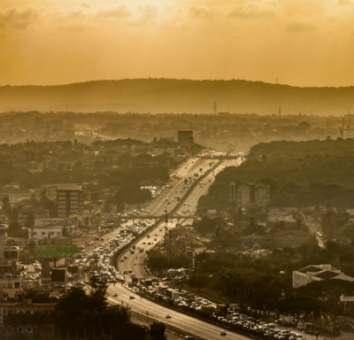 Hazy and sunny panoramic view of Accra, Ghana, including mountains and cars on highways