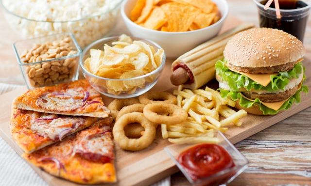 Ένα πιάτο επεξεργασμένου γρήγορου φαγητού που περιλαμβάνει μάρκες, σόδα, πίτσα, χάμπουργκερ και κρεμμύδια