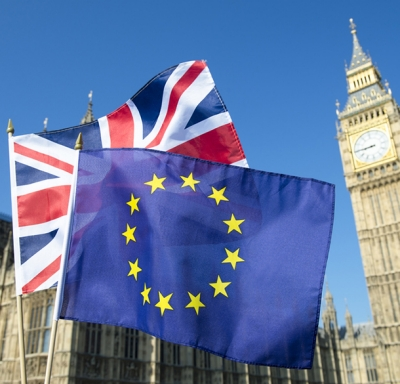 European Union and British Union Jack flags flying in front of Big Ben and the Houses of Parliament in London