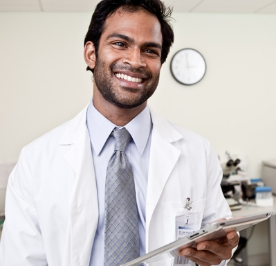 Doctor smiling and holding tablet