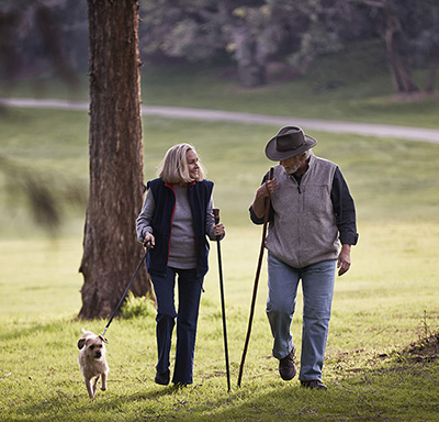 Middle-aged Caucasian couple walking their dog in a park