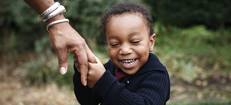 African-American boy holding hand of mother in park