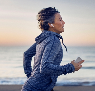 Mature woman listening to music while running along the beach