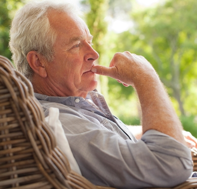 Pensive senior man sitting in wicker armchair on porch