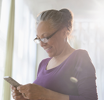 Middle-aged Hispanic woman smiling while using her smart phone