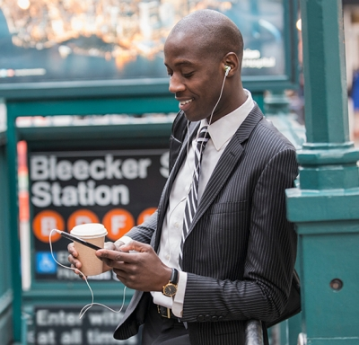 African-American businessman holding a cup of coffee while checking his cell phone near a New York City subway entrance.