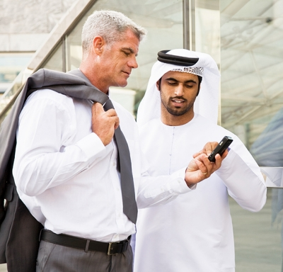 Caucasian businessman and an Arabic male colleague reading something on a cell phone.
