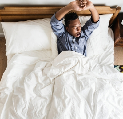 African-American man stretching and yawning as he awakens