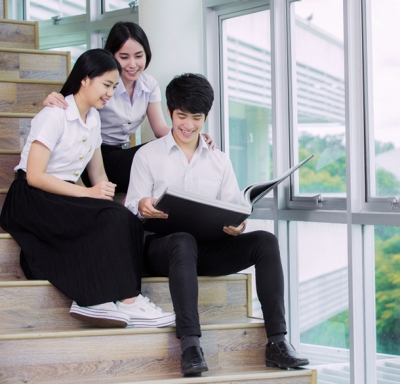 Group of Asian students at a Thai university reading and relaxing together