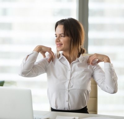 Smiling businesswoman stretching to relieve back and neck tension