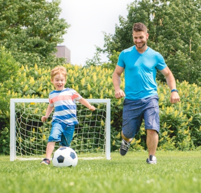 Father playing soccer with young son