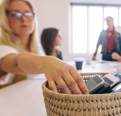 Woman placing mobile phone in basket with other phones