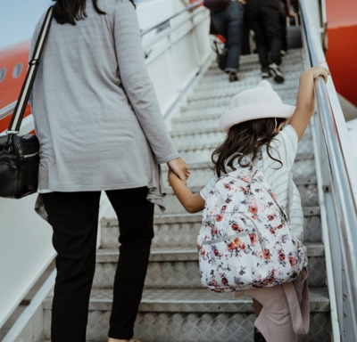 Asian mother holding her daughter's hand while walking up steps to board a plane