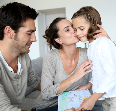 Mother kissing her daughter while the father looks at the picture the daughter drew for her mother