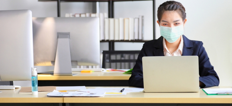 Woman wearing COVID-19 mask working in home office with hand sanitizer on desk