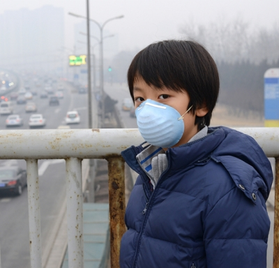 Asian boy wearing mouth mask to protect against air pollution