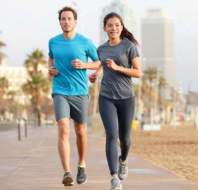 Caucasian male and Asian female jogging on Barcelona Beach in Barcelona, Spain