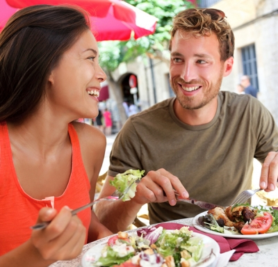 Couple smiling at each other while eating salad at an outdoor cafe