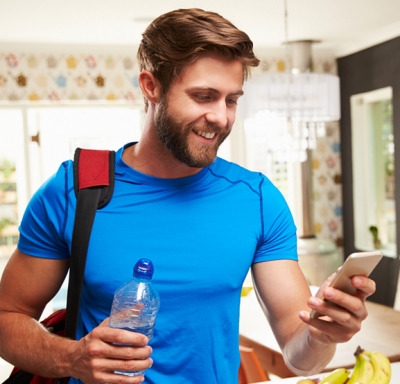 Caucasian male holding water bottle and looking at phone in his kitchen