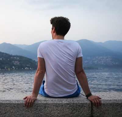 Athletic young man seated on a wall looking out at a lake and mountains