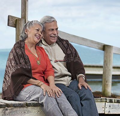 Older couple snuggled together while sitting on a dock overlooking water