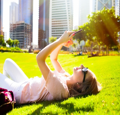 Woman lying on green lawn and checking her iPhone in the park
