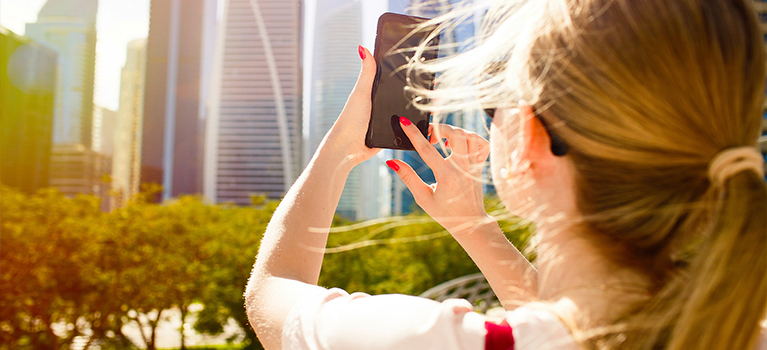 Woman taking picture of city Dubai skyline