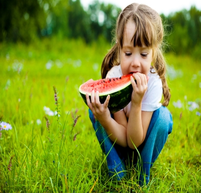Young girl sitting in a field while eating a wedge of watermelon
