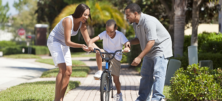 African-American mother and father helping son learn to ride a bicycle