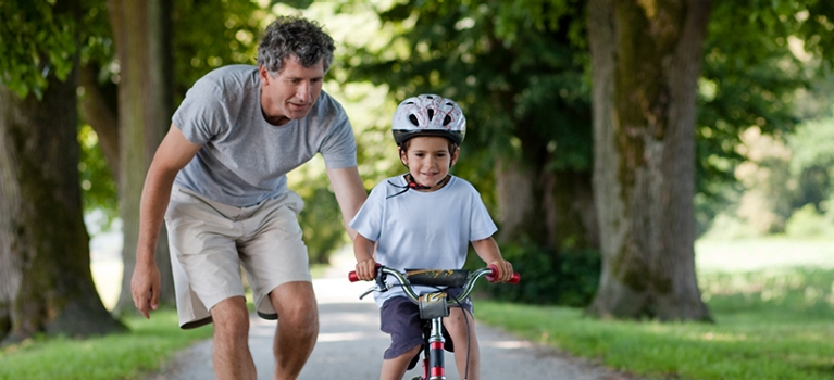 Father teaching young son to ride bicycle