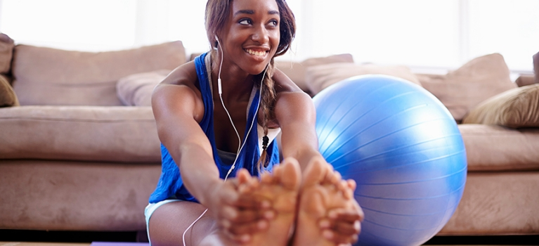 Young woman exercising and touching toes on sitting room floor