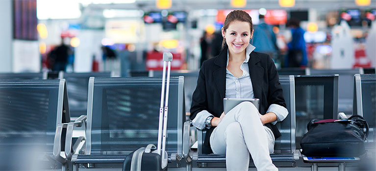 Young woman sitting at airport with luggage