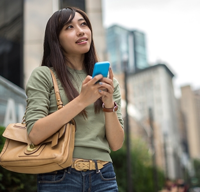 Korean woman looking around in city holding cell phone