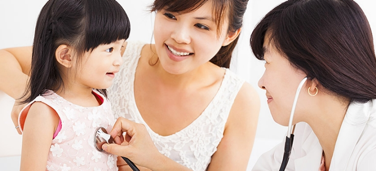 Asian doctor giving child examination