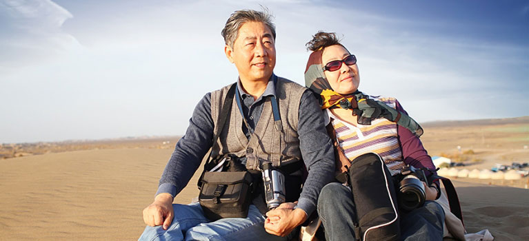 Travelling Asian couple on sand dune