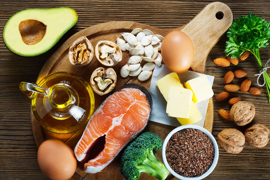 table full of foods rich in Omega 3s such as eggs, salmon, nuts, oils and seeds