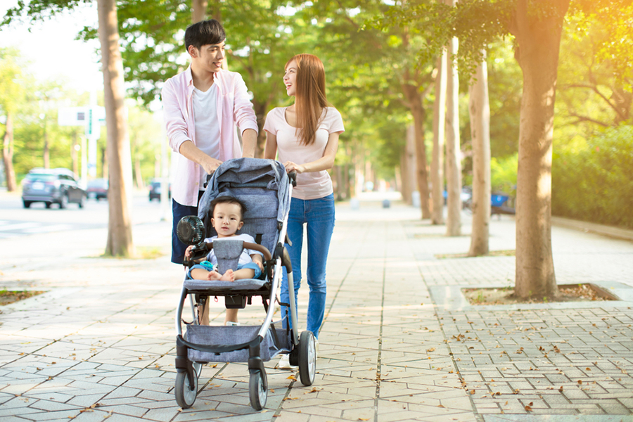 parents talking while walking baby in stroller down street